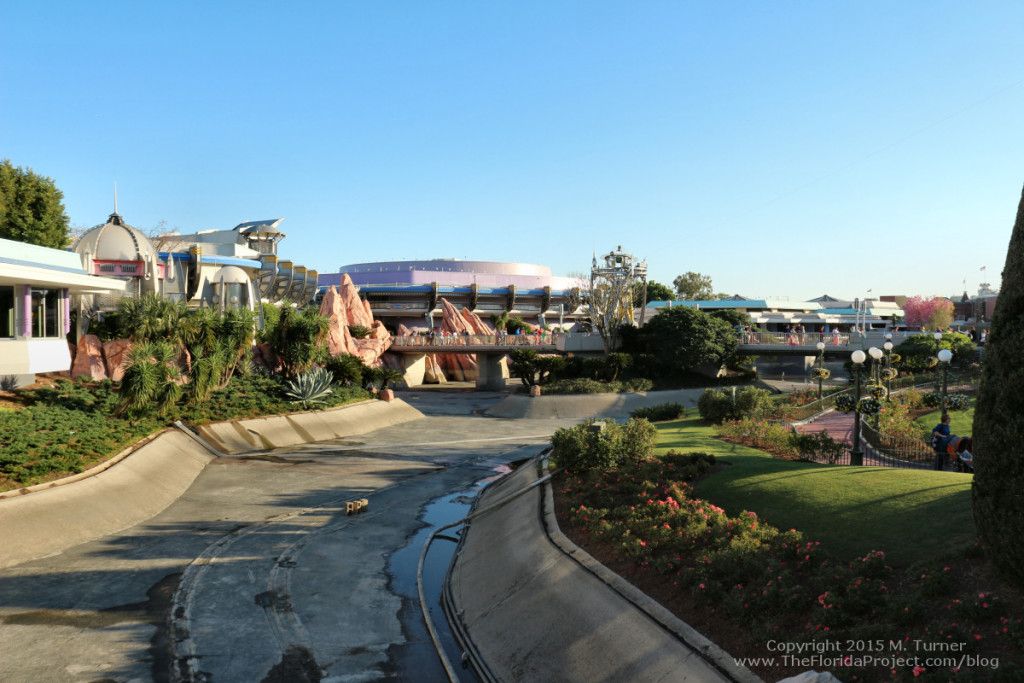 Drained and empty dry moat looking towards Tomorrowland and Cosmic Ray's Cafe, showing concrete, bricks and the old Swan Boat tracks. (Also shows rose garden where the old dock used to be but was removed in 2014.)